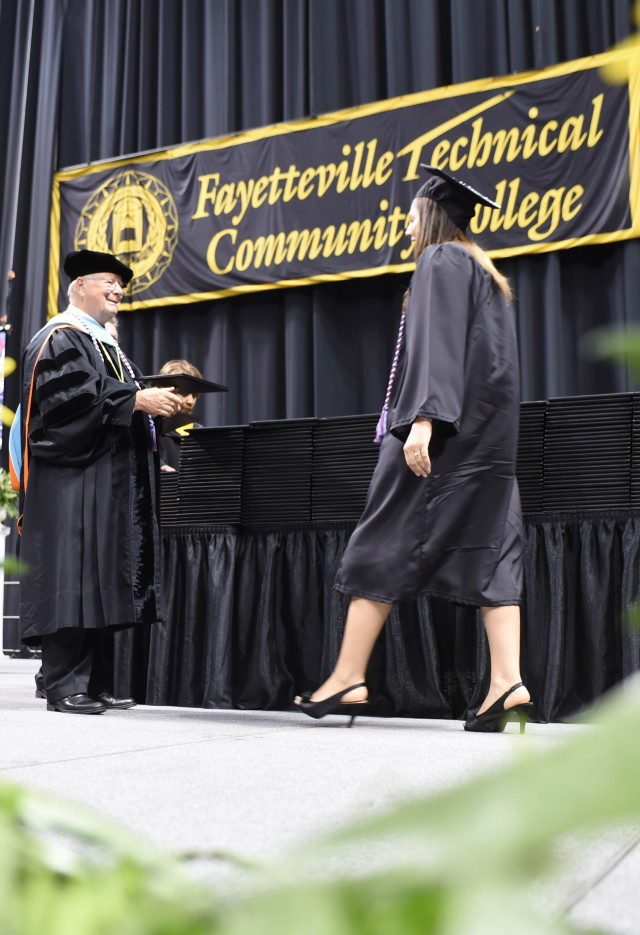 Woman receives her diploma at Graduation